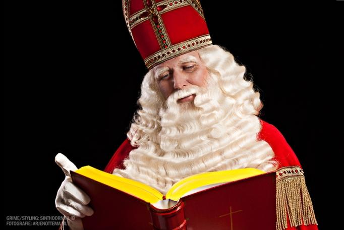 Sinterklaas leest in zijn grote boek