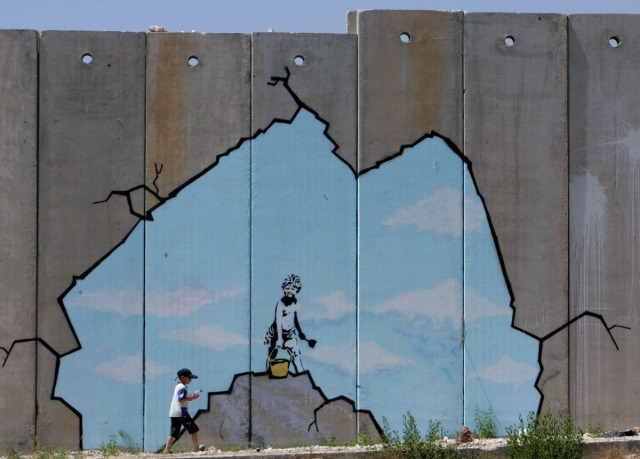 A Palestinian boy walks past a drawing by British graffiti artist Banksy near the Kalandia ...