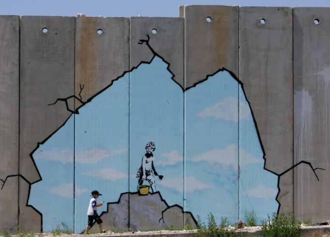 A Palestinian boy walks past a drawing by British graffiti artist Banksy near the Kalandia ...