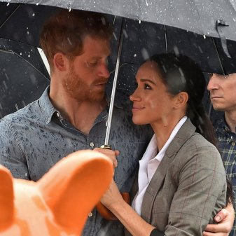 Britain's Prince Harry and his wife Meghan, Duchess of Sussex watch aboriginal dances at Victoria Park in Dubbo on October 17, 2018. - Prince Harry and his expectant wife Meghan visited a drought-stricken region of Australia on October 17, bringing a rare and welcome rainstorm with them. (Photo by Peter PARKS / POOL / AFP) (Photo credit should read PETER PARKS/AFP/Getty Images)